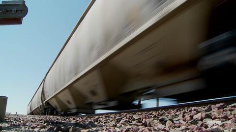 Low angle of a train passing with roadbed in foreground Footage