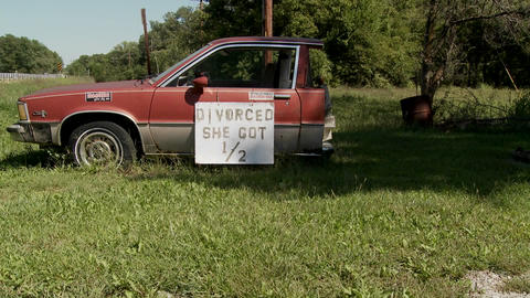 """A car is cut in half with the sign Divorced She Got 1/2"""" on it Footage"""
