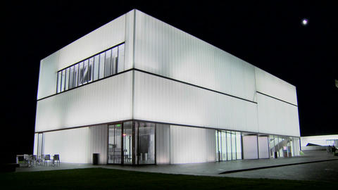 A modern building is illuminated and glows from the inside Footage