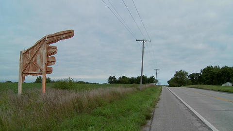 A large yellow sign points to Higginsville, Missouri from a farm field Footage