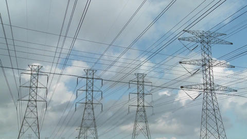 Time lapse of clouds moving behind high tension wires and... Stock Video Footage