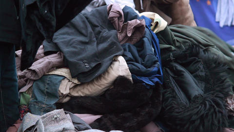 Clothes pile for poor people winter outdoor, male choosing coat Footage