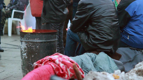 Poor people warming near fire trash barrel, winter outdoors Footage
