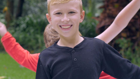 A cute smiling young blond boy waives his arms with his siblings waving theirs b Footage