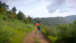 A man with a beard and a red umbrella walks towards the camera on a empty dirt r Footage