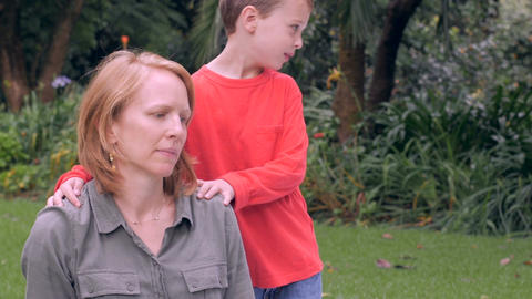 A nervous mother is concerned and distracted by something while her son massages Footage