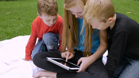Three cute sibling children sit on a blanket outside and play on a tablet in slo Footage