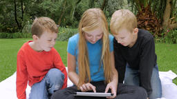 Three young children, brothers and sister, play together on a single tablet outs Footage