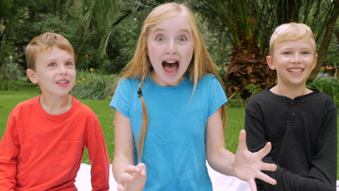 An older sister shows surprise while her youngest brother tries to imitate her w Footage