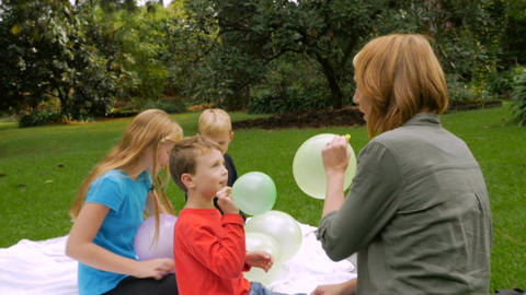 A family blowing up balloons lets them go as they fly away showing pure joy and Footage