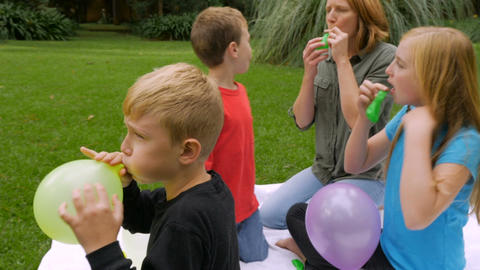 Side view handheld slowmo of a family of four blowing up balloons outside in a p Footage