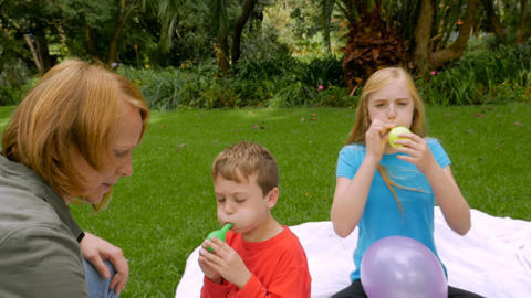 A redheaded mom comes to help her youngest son blow up balloons - slowmo steadic Footage