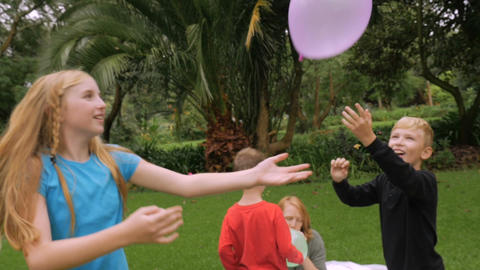 A family of four starts a simple game of hitting balloons in the air at a park - Footage