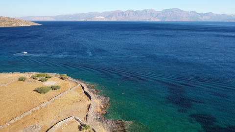 Aerial view of a speeding motor boat in a deep blue colored sea. Spinalonga Live Action