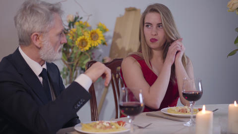 Young beautiful Caucasian woman seducing grey-haired man during romantic dinner Live Action