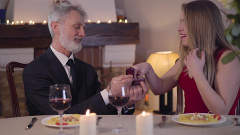 Confident senior man making marriage proposal to young woman during romantic Live Action