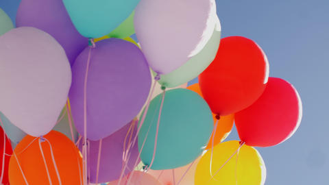 Many colorful balloons flying in blue sky background. Bunch colorful air balls Live Action