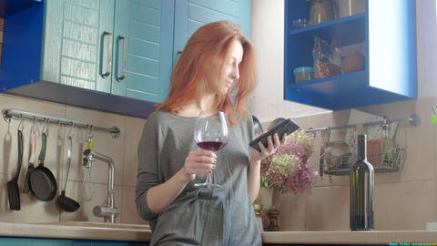 Attractive young redhead girl drinks wine at the weekend in the kitchen. Alcohol Live Action