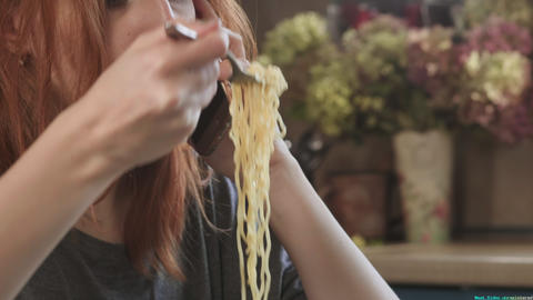 Attractive redhead girl eats instant noodles raft Mac and Cheese in the kitchen Live Action