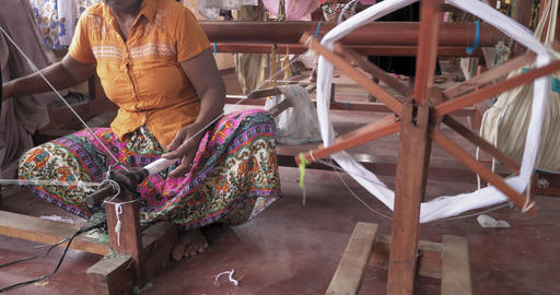 Hands of an old woman using an old spinning wheel to turn wool into yarn Live Action