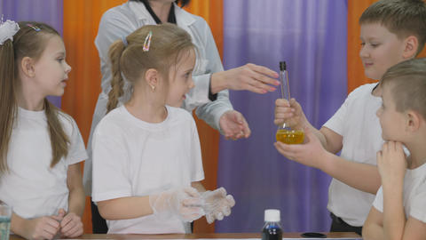 Chemical experiments for children. Children shake a flask , closed with a cork Live Action