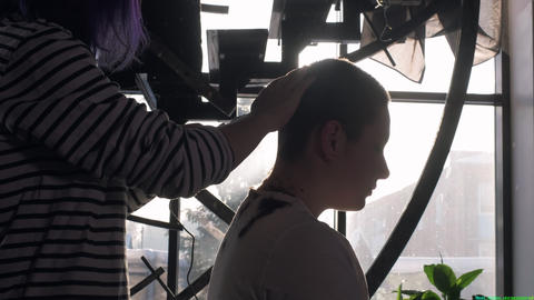 Young attractive girl shaves her hair on her head. Shaves his head with an Live Action