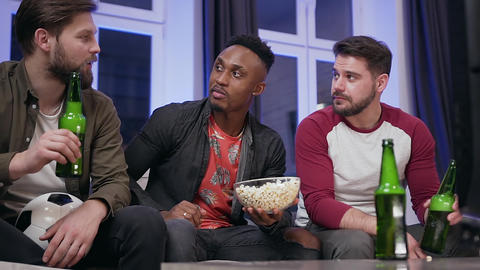 Attractive smiling modern mixed race guys eating popcorn and drinking beer while Live Action