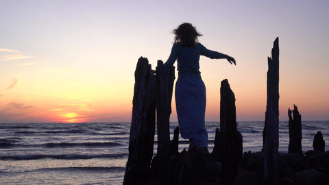 Romantic woman posing on old sea pier stones and woods on orange sunset Live Action