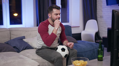 Handsome concentrated bearded young man eating chipps during reviewing the Live Action