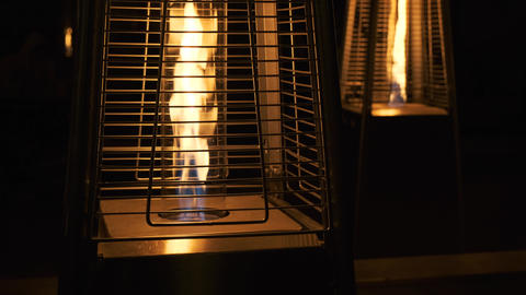 Gas heaters stand on the veranda, open cozy fire. Warmth and comfort. Flame of Live Action