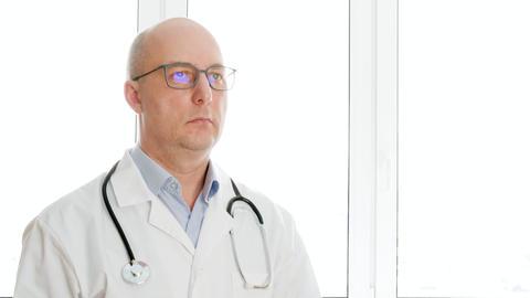 Confident doctor in eyeglasses nodding head Live Action
