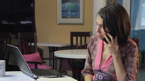 Woman in front of laptop receiving mobile phone call, internet Footage