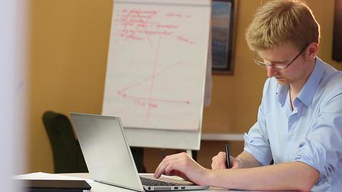 Laptop typing businessman writing making notes, financial index Footage