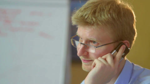 Businessman talks over phone says Hello to secretary close-up Footage