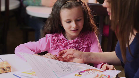 Mother shows happy little daughter color book, teaches colors Footage