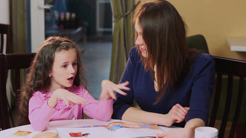 Woman mother teaching little girl daughter, learning process Footage