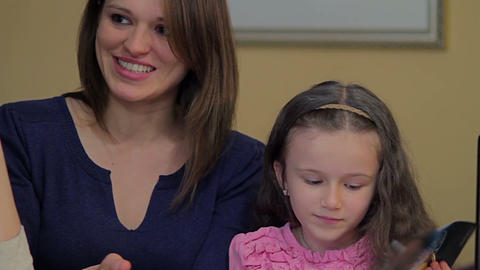Little daughter bored reads magazine, happy mother chats friend Footage