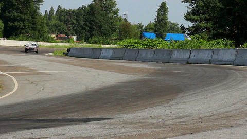 Race vehicles rushing in extremely hot pursuit on track curve Live Action