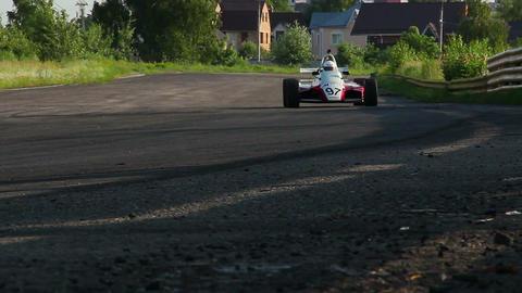 Formula 1 car driving desert circuit, taking fast turn Footage