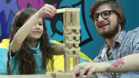 Little girl playing game happy young guy, building tower blocks Footage