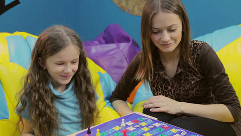 Girl teaches happy little sister, playing board game, having fun Footage
