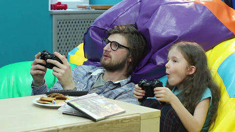 Young guy little girl playing video game, habit, game addiction Footage