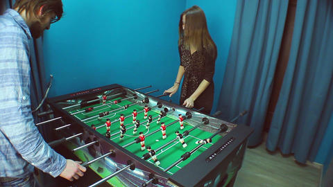 Young couple playing table football, communicating, having fun Footage