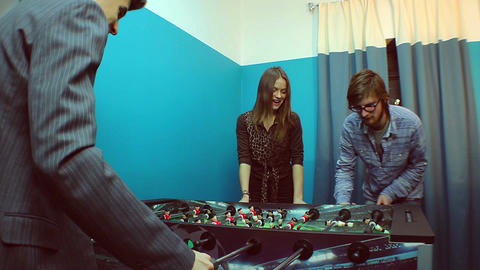 Two men woman having rest, playing table football, team-building Footage