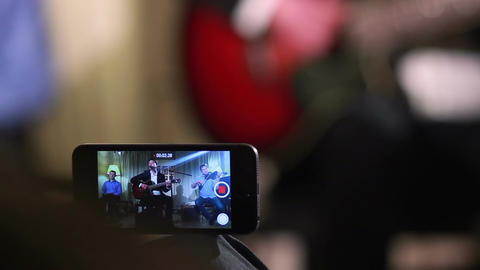 Shooting video of performance using phone, music band plays Footage