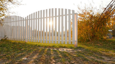 Picturesque landscape in the fall. Wooden fence with bright rays of the sun Live Action