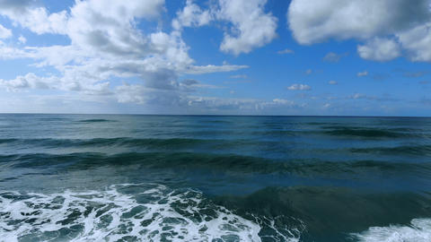 Fly over waves motion,aerial view on deep blue sea water,ocean horizon,cloud sky Live Action