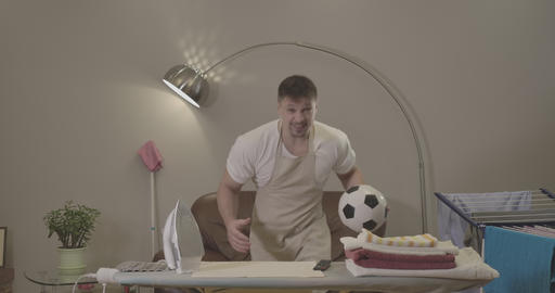 Joyful Caucasian man housekeeper with soccer ball cheering indoors. Handsome Live Action