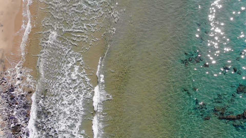 4K aerial drone view over splashing sea waves on wild sandy beach, fluid motion Live Action