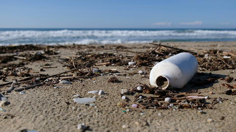 Plastic garbage on polluted beach over sea waves motion,dirty planet ecosystem Live Action